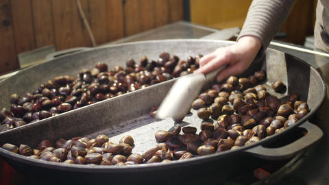Sweet chestnuts roasted on big pan in winter, hand stirs them up Footage