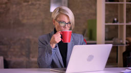 Portrait of blonde short-haired businesswoman in glasses attentively working Footage