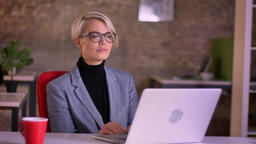 Portrait of blonde short-haired businesswoman in glasses attentively watching Footage