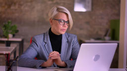 Portrait of middle-aged short-haired businesswoman in glasses talking in Footage