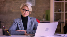 Portrait of blonde short-haired businesswoman in glasses smiling positively into Archivo