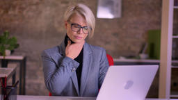 Blonde short-haired businesswoman in glasses working in office having sore Footage
