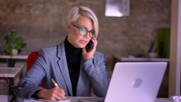 Blonde short-haired businesswoman in glasses talking on phone, working with the Footage
