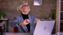 Portrait of middle-aged short-haired businesswoman in glasses dancing in her Footage