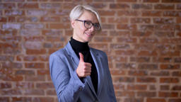 Portrait of middle-aged caucasian blonde short-haired woman in glasses gesturing Footage