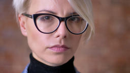 Close-up portrait of blonde short-haired woman in glasses watching seriously Footage