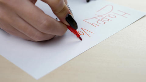 Woman writing letter with red pencil at Valentine's Day GIF