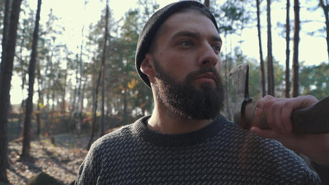 Brutal bearded man with an axe on his shoulder looking far ahead. Unshaven guy Live Action