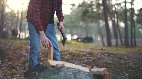 Man chops wood with axe in the forest. Forester cuts wood Footage