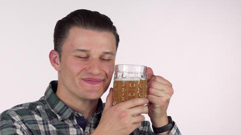 Happy young man smiling with eyes closed, cuddling with a mug of tasty beer Footage