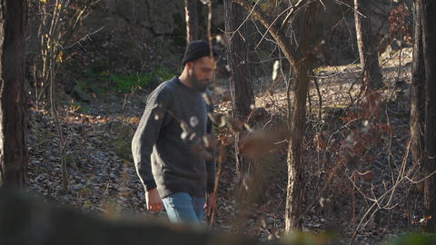 A man walk on the forest with ax in hands. Young bearded guy walks with an axe Live Action
