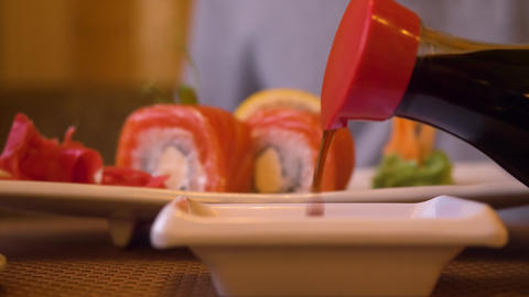 Pouring soy sauce for fresh japanese sushi roll in asian restaurant close up Footage