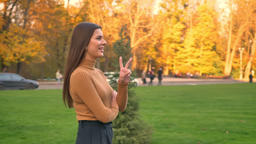 Portrait of attractive young brunette girl walking and gesturing peace sign with Footage