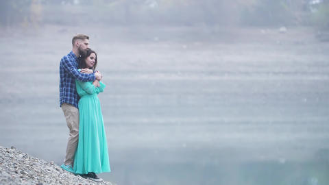 a stylish couple man and woman on the background of the lake GIF