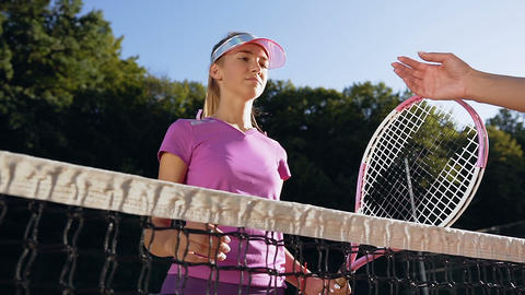 Portrait shot of cute girl shaking hands over the tennis court net to another Footage
