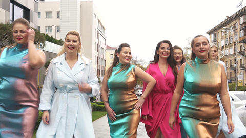 Beautiful women in fashion dresses defile on the street. Plus size Fashion Week Live Action