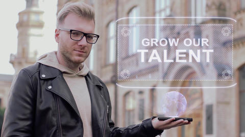 Smart young man with glasses shows a conceptual hologram Grow our talent Footage