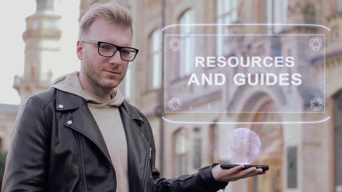 Smart young man with glasses shows a conceptual hologram Resources and guides ビデオ