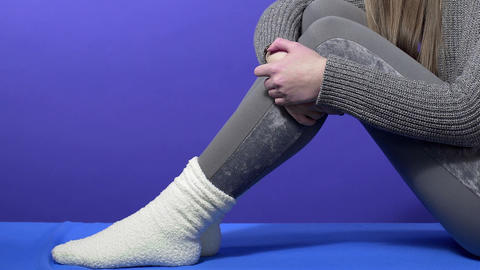 Woman wiggles her legs in warm socks, warm winter clothes, women's warm clothing Live Action