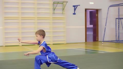 Young caucasian boy in national Chinese dress is practicing Kung Fu wushu tai Footage