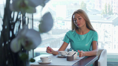 Gorgeous woman drinking tea, waiting for someone at the restaurant for breakfast Live Action