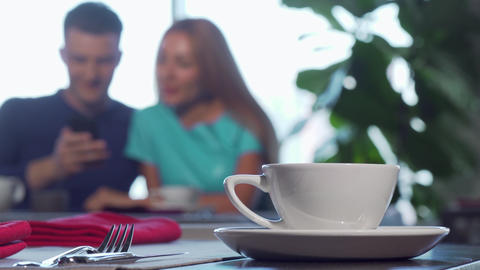 Selective focus on a cup on the table, couple cuddling on the background ライブ動画