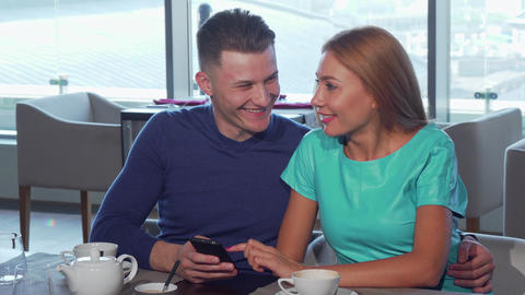 Happy loving couple embracing, using smart phone at the cafe together Live Action