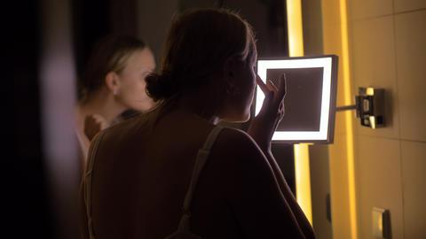 Woman looking in bathroom mirror after applying facial cream Live Action