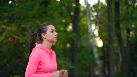 Close up of woman running through an autumn park at sunset. Slow motion ビデオ