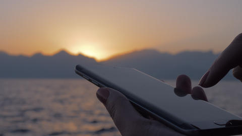 Woman using cellphone on sea and sunset background Live Action