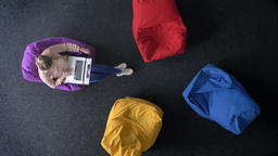 Top-shot of young woman working with laptop on soft multicoloured bags changing ビデオ