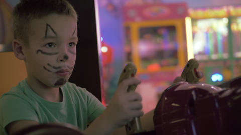 A boy with a painted cat snout on a face playing a game machine Live Action