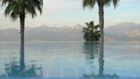 Outdoor swimming pool with palms and mountains scene Footage