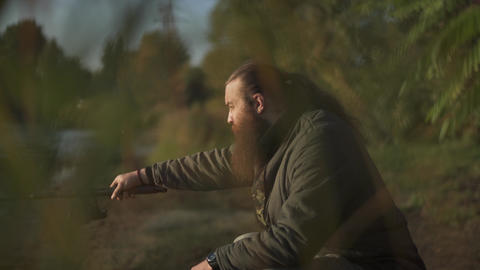 Bearded fisherman fishing with fishing pole. Fisher focuses on fishing Footage