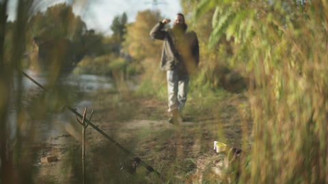 Bearded man moves toward the camera and looks on the water. The rod is fixed in Footage