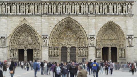 Tourists walking near Notre-Dame western facade, gothic architecture, Paris Footage