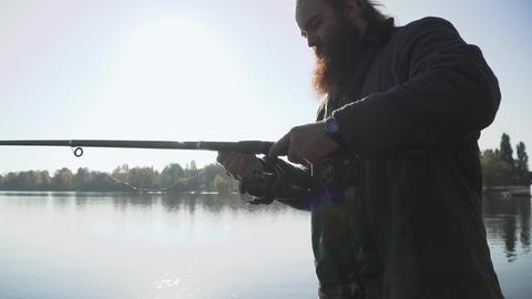 Bearded fisherman adjusts fishing rod. Fisher preparing for fishing. Fishing on Footage
