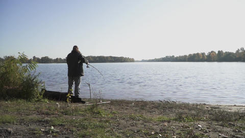 Fisherman with beard is fishing on the river bank. Man fishing with a fishing Live Action