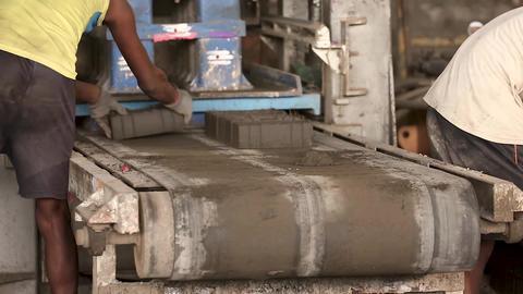 Bricks on the conveyor belt, worker unloads bricks Footage
