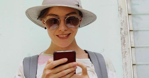 Stylish female using smartphone near shabby building Footage