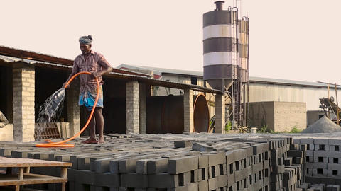 Part of a small dirty old cement plant. Man water spray in Cement Brick Live Action