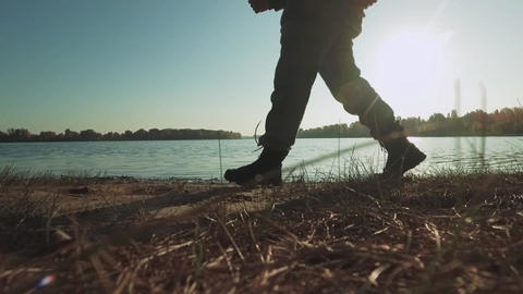 Male legs walking in the sunshine near the river ビデオ