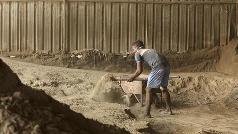 Caucasian worker pours sand into a concrete mixer with shovel at construction Live Action