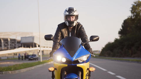 A motorcyclist rides a city on his yellow-blue motorcycle in a helmet and a Live Action