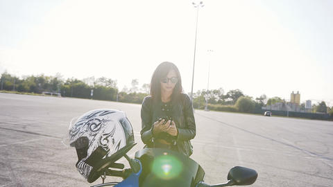 A young biker girl in a leather jacket and sunglasses sitting on his motorcycle Live Action