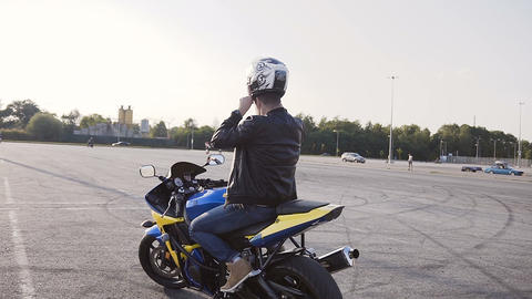 Motorcyclist on a sunset sits down on a motorcycle, wears a helmet and goes to Live Action