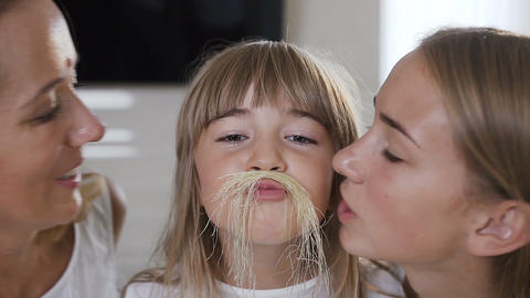 Close-up charming little girl with long hair makes a mustache from corn hair and Footage