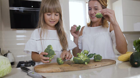Mom with her daughter having fun in kitchen with healthy food. Happy fun mom Live Action