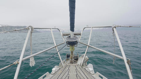 Sailboat bow sailing in blue ocean water and snowy islands landscape Footage