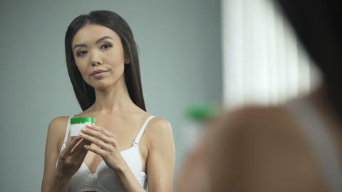 Beautiful Asian girl putting cream on face, standing in front of mirror, beauty Footage